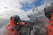 """Sea Shepherd crew in an inflatable fast boat, armed with bottles of rotten butter, are doused by sea spray and water cannons from Japanese harpoon ship, the Yushin Maru No. 1, on Thursday, Feb. 5, 2009 during a confrontation in Antarctica's Ross Sea.  The whaling fleet reported a final tally of 679 minke whales and one fin whale caught during this season's five-month effort, falling short of its goal of 935 minkes and 50 fins.  Officials blamed poor weather and """"interference by protesters"""". (Photo by Adam Lau)"""