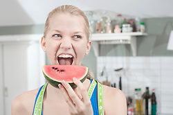 Young woman eating slice of watermelon in the kitchen, Bavaria, Germany
