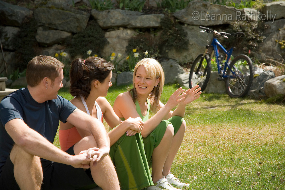 A trio of people relax before a bike ride.