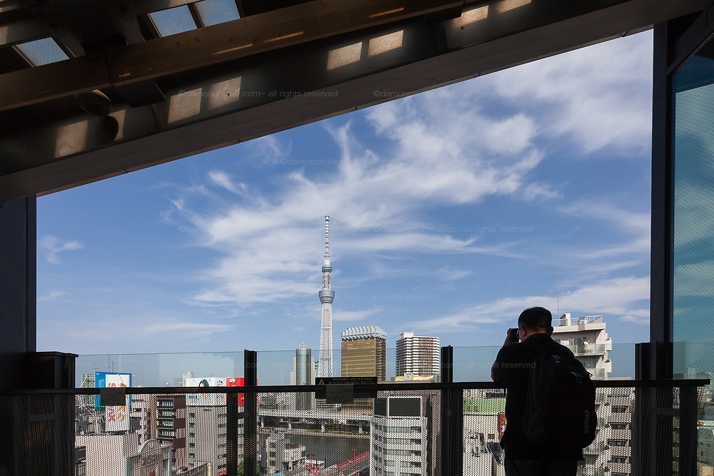 A tourist takes a photo of Tokyo Skytree from the Tourist Center in Asakusa, Tokyo, Japan. Thursday June 28th 2018