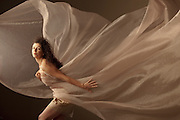 A woman's dress flys in the air with the wind