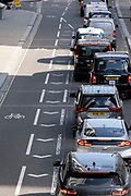 Alongside an empty cycle lane, queues of traffic wait for a green light on London Wall in the City of London, the capital's financial district, on 21st September 2021, in London, England. Post-Covid pandemic, City workers are returning to their office desks in greater numbers but many still prefer to work from home for at least 1-2 days a week.