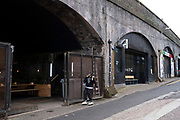 Man rollerblading near railway arches in Digbeth on 14th March 2020 in Birmingham, United Kingdom. Digbeth is an area of Central Birmingham, England. Following the destruction of the Inner Ring Road, Digbeth is now considered a district within Birmingham City Centre. As part of the Big City Plan, Digbeth is undergoing a large redevelopment scheme that will regenerate the old industrial buildings into apartments, retail premises, offices and arts facilities. There is still however much industrial activity in the south of the area.