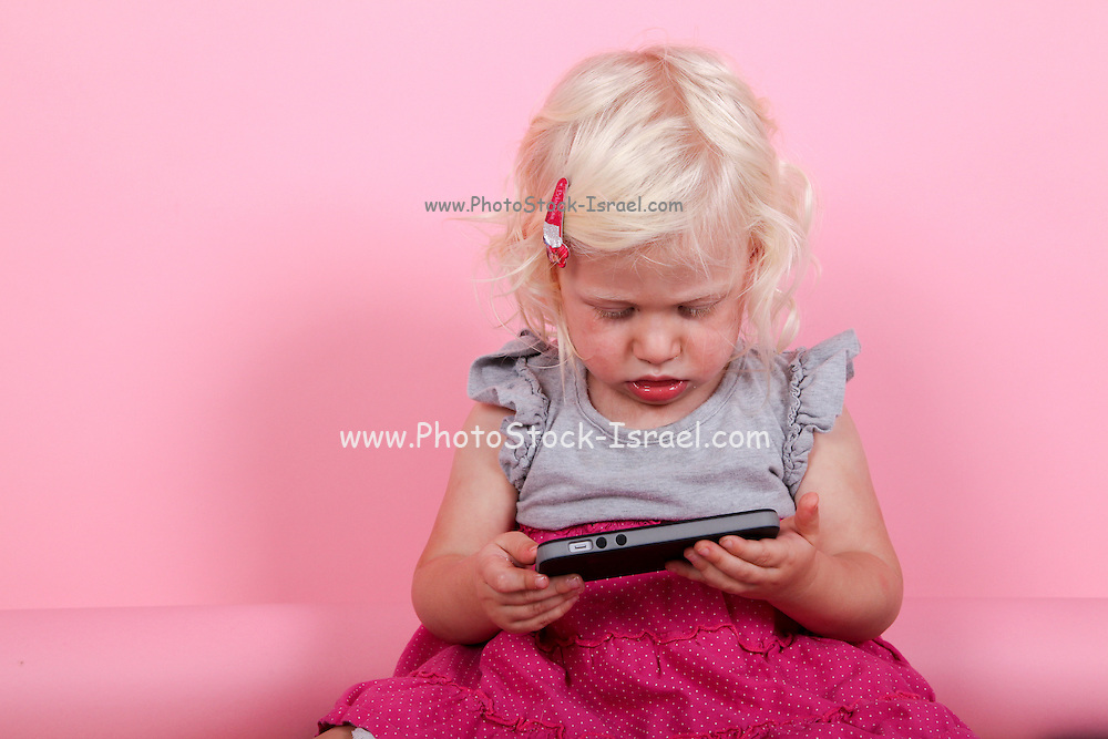 young blonde girl of two, plays with an iPhone on pink background. Model release available