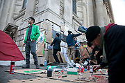 Poster making, London Hug Exchange. Day three of the occupation - and the first Monday. The Occupy London Stock Exchange movement was formed in London in solidarity with the US based Occupy Wall Street. The movements are a respons and in anger to what is seen by many as corporate greed and a failed banking system being bailed out by the public, - which in return are suffering austerity measures to make up for the billions of lost money. The movement occupied the St Paul's Square in the City of London Sat Oct 15 after it failed to secure and occupy Pator Noster Square and the Stock Exchnage itself.