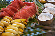 Tropical fruits, bananas, watermelons and shaved coconut snack treats served on palm leaves in Bora Bora