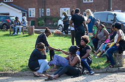 © Licensed to London News Pictures. 15/09/2016. London, UK. Grieving relatives, including the sister of a victim (pictured wearing blue dress) at scene of a double shooting in a block of flats in East Finchley. Police were called by London Ambulance Service at 06:25hrs this morning to reports of two people injured at an address in north London. A man and a woman were found with gunshot injuries. Both were pronounced dead at the scene. Photo credit: Ben Cawthra/LNP