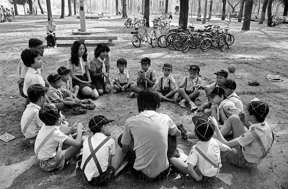 A Saigon cub pack meet to reaffirm the code they have learned. The North Vietnamese army (Viet Cong) are approaching on the outskirts of the capital city. This could well be their last meeting as the communist north have banned Cub, scout and guide packs. The Vietnam War was fought between 1st November 1955 until the fall of Saigon on 30 April 1975. Photographed by Terry Fincher.