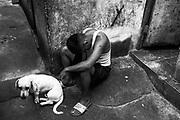 R.R. (21), paciente con tuberculosis multidrogorresistente (TB-MDR), sentado en el pasadizo del lugar donde vive, en el Cerro San Cosme en el distrito de La Victoria (Lima). En septiembre del 2019 le detectaron la enfermedad y desde noviembre del mismo año empezó su tratamiento por nueve meses. Toma 13 pastillas cada día. Vive junto con su madre y hermanas en una habitación prefabricada de madera, en un edificio de cuatro pisos habitado por más de 30 familias. Su madre se encarga de recoger sus pastillas para que no deje el tratamiento. Perú. 6 de marzo del 2020.