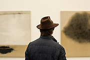 New York, NY - May 3, 2019. A man in a fedora with Ryuji Tanaka's oils in the Axel Vervoordt Gallery at the Frieze Art Fair on New York City's Randalls Island.