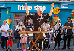 Edinburgh, Scotland, UK. 4th August  2021.  Edinburgh City Centre and Old Town busy this afternoon in warm sunny weather. Pic; Street performer drew big crowd during his magic trick show on the Royal Mile.  Iain Masterton/Alamy Live news.