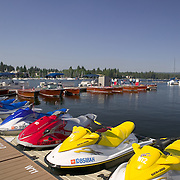 Idaho, Valley County, McCall, Payette Lake. Personal water craft at dock with classic wooden boats in background, McCall Wood Boat Show.