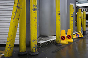 Yellow vehicle bollards to protect fragile structure at SMithfield meat market, City of London.