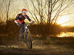 Mature man riding mountain bike on dirt track, Bavaria, Germany