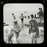 Magic lantern slide of children boys and girls paddling playing in the sea, UK circa 1900