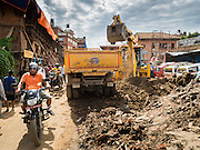 02 AUGUST 2015 - BHAKTAPUR, NEPAL:   A man in Bhaktapur rides his motorcycle past a crew removing debris from the earthquake that hit Nepal in April 2015. Bhaktapur was badly damaged in the earthquake the hit Nepal in April 2015. The Nepal Earthquake on April 25, 2015, (also known as the Gorkha earthquake) killed more than 9,000 people and injured more than 23,000. It had a magnitude of 7.8. The epicenter was east of the district of Lamjung, and its hypocenter was at a depth of approximately 15 km (9.3 mi). It was the worst natural disaster to strike Nepal since the 1934 Nepal–Bihar earthquake. The earthquake triggered an avalanche on Mount Everest, killing at least 19. The earthquake also set off an avalanche in the Langtang valley, where 250 people were reported missing. Hundreds of thousands of people were made homeless with entire villages flattened across many districts of the country. Centuries-old buildings were destroyed at UNESCO World Heritage sites in the Kathmandu Valley, including some at the Kathmandu Durbar Square, the Patan Durbar Squar, the Bhaktapur Durbar Square, the Changu Narayan Temple and the Swayambhunath Stupa. Geophysicists and other experts had warned for decades that Nepal was vulnerable to a deadly earthquake, particularly because of its geology, urbanization, and architecture.      PHOTO BY JACK KURTZ