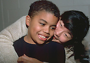 Leader hugging boy age 27 and 10 in community youth group.  St Paul Minnesota USA