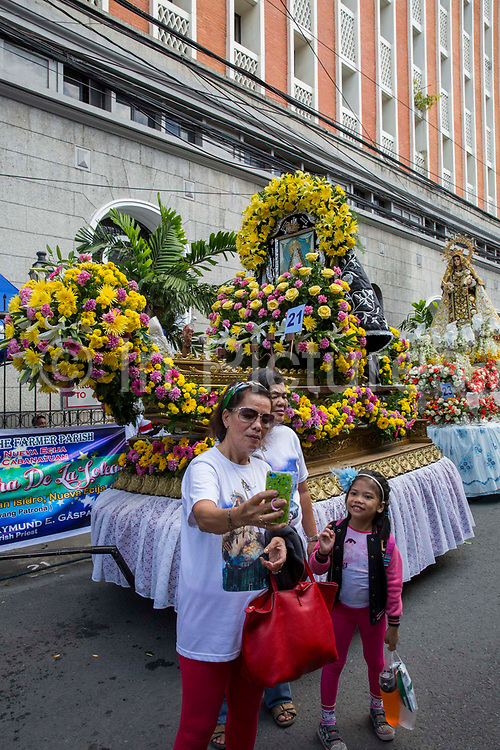 Tourists and locals taking pictures with one of the floats from the Grand Marian Procession in Intramuros, Metro Manila, Philippines.