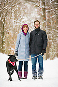 Portrait of couple with three-legged dog who loves the snow in Carlise, MA