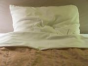 a slightly ruffled pillow on a bed