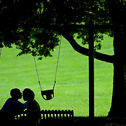 """Mario Blunt, left, and Kayla Hansley, right, relaxed on a park bench in the shade in Loose Park on Monday afternoon. Blunt said """"we're enjoying the last days of summer."""" When asked if they were a couple, Blunt said """"we're working on that..."""""""