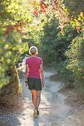 Rear view of female hiker walking on path amidst trees, Pegeia, Cyprus