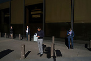 City workers on their cell phones within street scene of light and shadow in the City of London, England, United Kingdom. (photo by Mike Kemp/In Pictures via Getty Images)