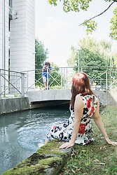 Man taking photograph of woman sitting at the edge of Eisbach River