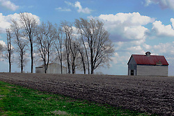 2012, March 18:  A farm building, Barn or crib sits idle in the barn lot with part of the roof missing accompanied by a newer machine shed.