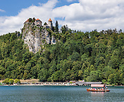 """A Pletna boat paddles across Lake Bled under the medieval Bled Castle (Slovene: Blejski grad, German: Burg Veldes), which was built a little before 1011 AD on a cliff above the city of Bled, in what is now Slovenia, Europe. The distinctive two-paddle Pletna boats originated in 1590 and can carry 20 people. A colourful awning protects passengers from sun and weather. The respected title of """"Pletnarstvo,"""" Pletna oarsman, has been handed down within specific families from generation to generation."""