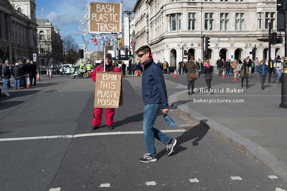 On the occasion of Commonwealth Day, a man carrying a plastic bottle walks past an environmental activist standing in Parliament Square, advocating the ban on plastics around the world, on 11th March 2019, in Westminster, London, England.
