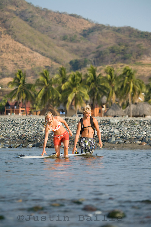 Young man and woman going surfing in Mexico.
