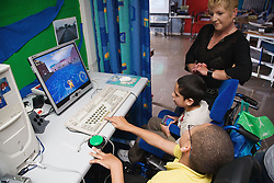 Children with physical and learning disabilities playing computer games in an IT lesson,