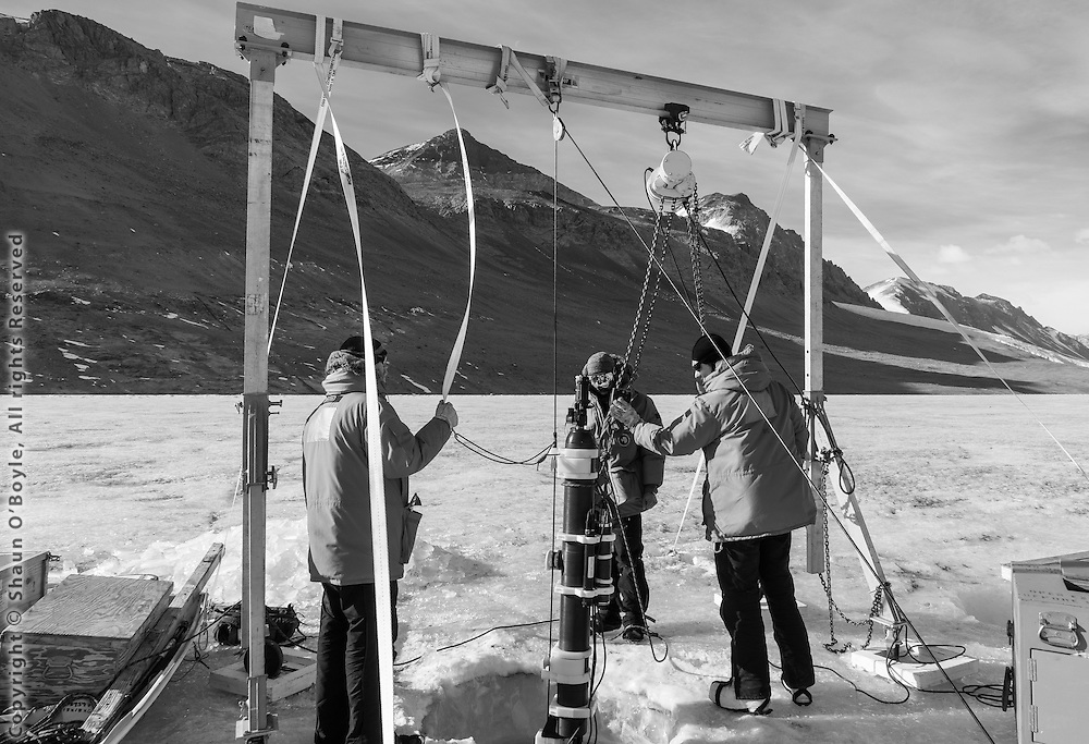 Scientist working on the LTER (Long Term Ecological Research) project on Lake Bonney preparing a robot that samples the lake water column throughout the year. The original objectives of the McMurdo LTER were to understand the influence of physical and biological constraints on the structure and function of dry valley ecosystems and to understand the modifying effects of material transport on these ecosystems. Now in the third funding cycle, they are poised to answer more complex questions about biodiversity, the impact of climatic legacies, and ecosystem structure and function.
