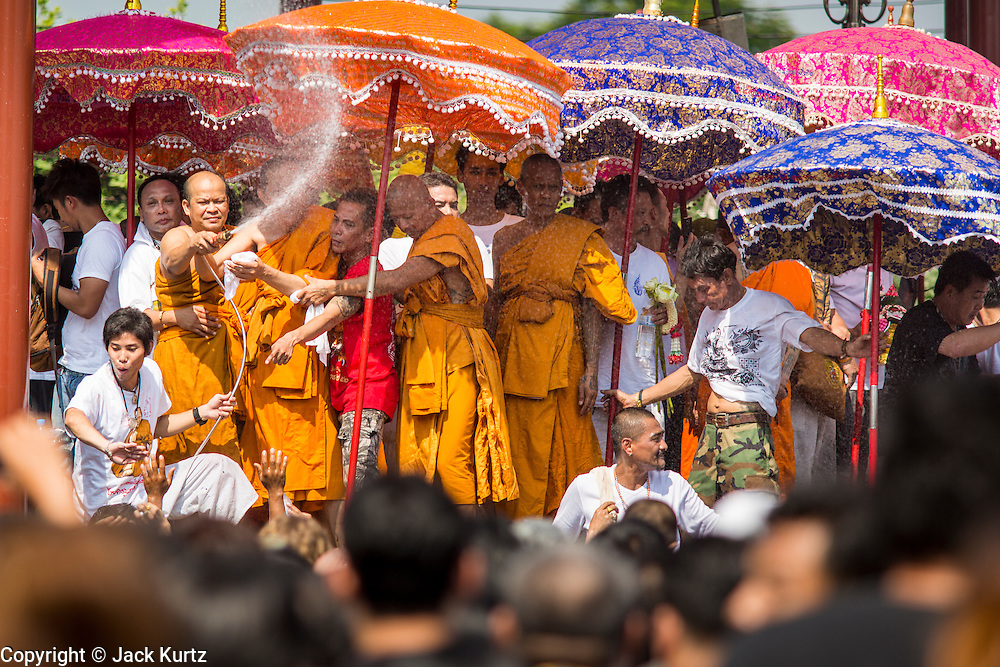 """23 MARCH 2013 - NAKHON CHAI SI, NAKHON PATHOM, THAILAND:  Monks spray the crowd with fire hoses at the end of the Wat Bang Phra tattoo festival. The fire hoses both break up the crowd and cools them down after the several hour long Buddhist service in the mid day sun. Wat Bang Phra is the best known """"Sak Yant"""" tattoo temple in Thailand. It's located in Nakhon Pathom province, about 40 miles from Bangkok. The tattoos are given with hollow stainless steel needles and are thought to possess magical powers of protection. The tattoos, which are given by Buddhist monks, are popular with soldiers, policeman and gangsters, people who generally live in harm's way. The tattoo must be activated to remain powerful and the annual Wai Khru Ceremony (tattoo festival) at the temple draws thousands of devotees who come to the temple to activate or renew the tattoos. People go into trance like states and then assume the personality of their tattoo, so people with tiger tattoos assume the personality of a tiger, people with monkey tattoos take on the personality of a monkey and so on. In recent years the tattoo festival has become popular with tourists who make the trip to Nakorn Pathom province to see a side of """"exotic"""" Thailand. The 2013 tattoo festival was on March 23.    PHOTO BY JACK KURTZ"""