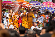 "23 MARCH 2013 - NAKHON CHAI SI, NAKHON PATHOM, THAILAND:  Monks spray the crowd with fire hoses at the end of the Wat Bang Phra tattoo festival. The fire hoses both break up the crowd and cools them down after the several hour long Buddhist service in the mid day sun. Wat Bang Phra is the best known ""Sak Yant"" tattoo temple in Thailand. It's located in Nakhon Pathom province, about 40 miles from Bangkok. The tattoos are given with hollow stainless steel needles and are thought to possess magical powers of protection. The tattoos, which are given by Buddhist monks, are popular with soldiers, policeman and gangsters, people who generally live in harm's way. The tattoo must be activated to remain powerful and the annual Wai Khru Ceremony (tattoo festival) at the temple draws thousands of devotees who come to the temple to activate or renew the tattoos. People go into trance like states and then assume the personality of their tattoo, so people with tiger tattoos assume the personality of a tiger, people with monkey tattoos take on the personality of a monkey and so on. In recent years the tattoo festival has become popular with tourists who make the trip to Nakorn Pathom province to see a side of ""exotic"" Thailand. The 2013 tattoo festival was on March 23.    PHOTO BY JACK KURTZ"