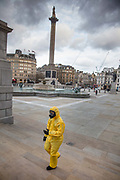 Extream caution was being followed by a young man crossing a normally crowded Trafalgar Square which was deserted as Coronovirus clampdown began on Friday evening on 20th March 2020 in London, United Kingdom. Although few in the United Kingdom wear masks the demand for surgical face masks in China has reached a cumulative 200 million masks a day.