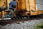 A migrant climb up to the train in movement. Migrants fall down on the train tracks frequently and suffer serious injuries where lose their legs, arms, even their lives, in State of Mexico, Mexico, May 20, 2008.