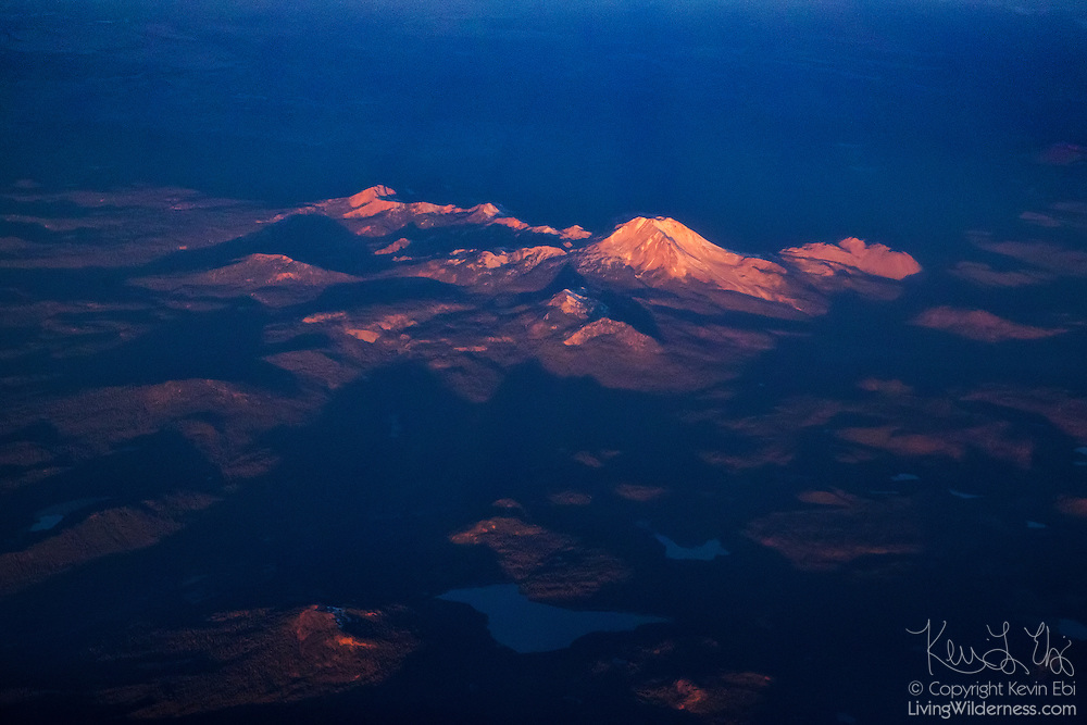 Lassen Peak, a 10,457-foot (3,187-meter) volcano, in the Cascade Range in California, is lit by the first light of day in this aerial view over Lassen Volcanic National Park. Lassen Peak, also known as Mount Lassen, is an active volcano that last erupted in 1917. The area, however, is still volcanically active with hot springs, geysers and boiling mud pots. Lassen Peak itself stands near Mount Tehama, which was a stratovolcano that was once at least 1,000 feet taller than Lassen Peak is now. Mount Tehama is now known as Brokeoff Mountain, and is visible to the left of Lassen Peak in this image.