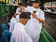 16 APRIL 2015 - BANGKOK, THAILAND:  A man gets a haircut at a barber school that sets up on the platform at Hua Lamphong Train Station in Bangkok. Travelers get free haircuts and the barber students get to practice on real heads.    PHOTO BY JACK KURTZ