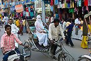 Street scene in holy city of Varanasi, young muslim woman wearing traditional burka rides in rickshaw, Benares, Northern India