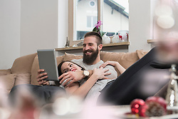 Couple watching digital tablet, relaxing on sofa