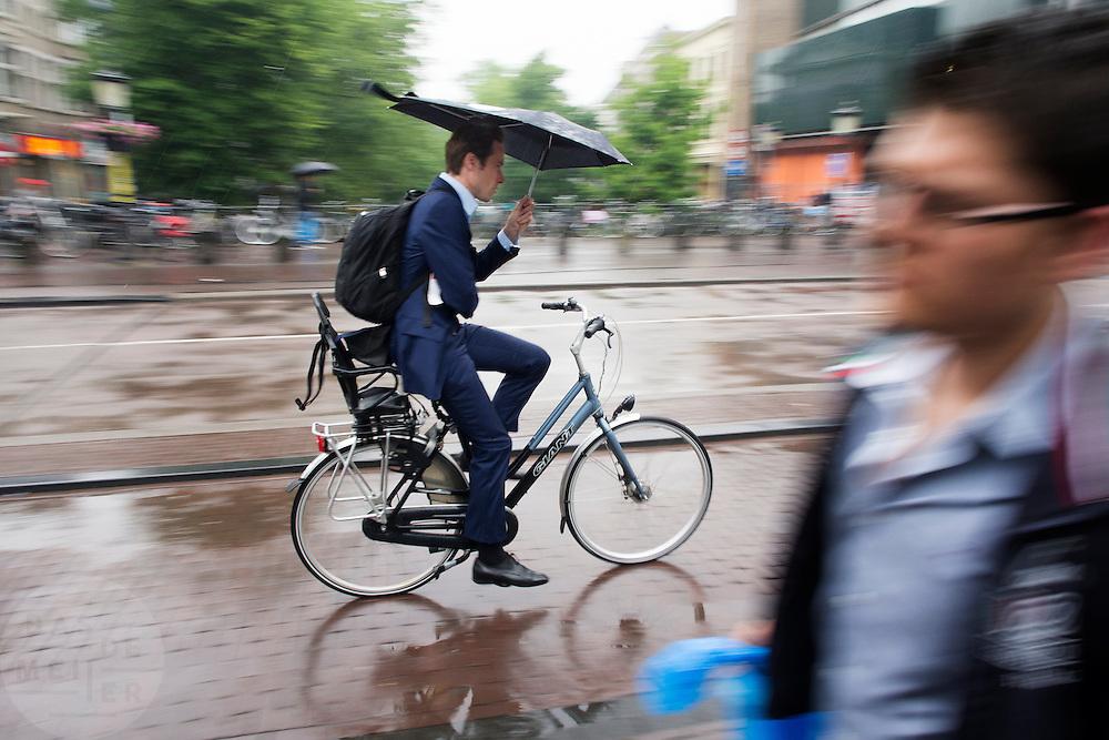 In Utrecht fietst een zakenman door de regen.<br /> <br /> In Utrecht a business man is cycling in the rain.