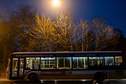 Street lamp shines out illuminating some trees above a passing bus on a frosty evening on 30th December 2020 in Birmingham, United Kingdom.
