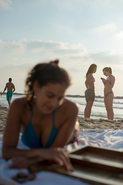 """An Israeli woman plays backgammon (""""shesh besh"""" in Israel) late on a Saturday afternoon at the beach in Tel Aviv. Two young ladies are in the backround, one texting on her phone."""