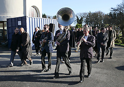 © Licensed to London News Pictures. 09/12/2015. London, UK. A brass band following the funeral procession as it arrives at the service... The funeral of former brothel keeper Cynthia Payne takes place at the South London Crematorium.  In 1980 Cynthia Payne was sentenced to 18 months for running a brothel at her house on Ambleside Avenue in Streatham. It was alleged, at the time, that judges and Members of Parliament were visitors to her establishment. Photo credit: Peter Macdiarmid/LNP