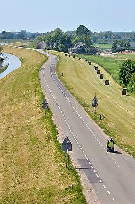 Nederland, Andelst, 8-6-2013Een oudere man rijdt op zijn scootmobiel over de dijk.Foto: Flip Franssen/Hollandse Hoogte