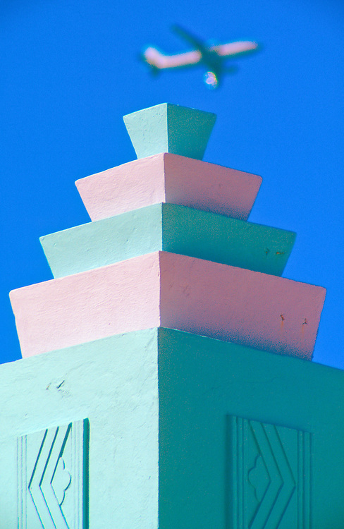 A  jet airliner soars over a decorative tower on Miami Beach's Art Deco-style MacArthur Hotel, designed by architect T. Hunter Henderson in 1930.<br /> <br /> The pastel pink and Necco wafer green color scheme on this landmark building was created much later, in the 1980s, by preservation activist Leonard Horowitz, whose pastel vision for the neighborhood helped launch a renaissance.