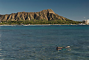 Snorklers at Waikiki Beach with Diamond Head Crater in the background.