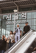 People, including a South Korean Navy sailor, descend an escalator outside Seoul Station, the main train station in the South Korean capital. (September 27, 2019)